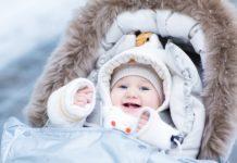 Radosne dziecko w zimowym śpiworku do wózka